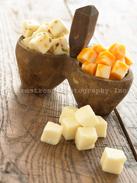 Cubes of colby, pepper jack, and white cheddar on a wooden table.