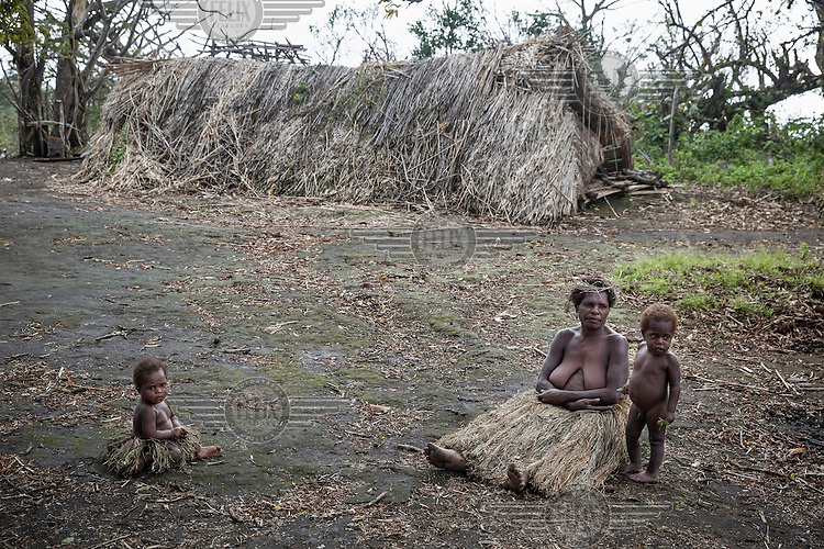 A women and children from Yakel village on Tanna Island are seen in front of a collapsed house that was destroyed by Cyclone Pam. Yakel village is known for its preservation of traditional lifestyle and culture and is a tourist attraction. The village was damaged by Cyclone Pam and locals lost their homes and gardens. Since much of the tourist trade stopped after the Cyclone hit the country, Yakel people also lost their income from foreign visitors.<br /> Cyclone Pam, a tropical storm that hit the Pacific island nation of Vanuatu on 13 March 2015, is considered one of the worst natural disasters to affect the country. Over 15 people died in the storm and winds up to 165 mph (270 km/h) caused widespread damage to houses and infrastructure.