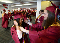 NWA Democrat-Gazette/ANDY SHUPE<br /> Taylor Voight (right) helps fellow Rogers New Technology School senior Sidra Nadeem Wednesday, May 15, 2019, with her mortar board and stole and sashes before the start of the school's commencement exercises in Barnhill Arena on the University of Arkansas campus in Fayetteville. The school graduated about 170 seniors during the ceremony.