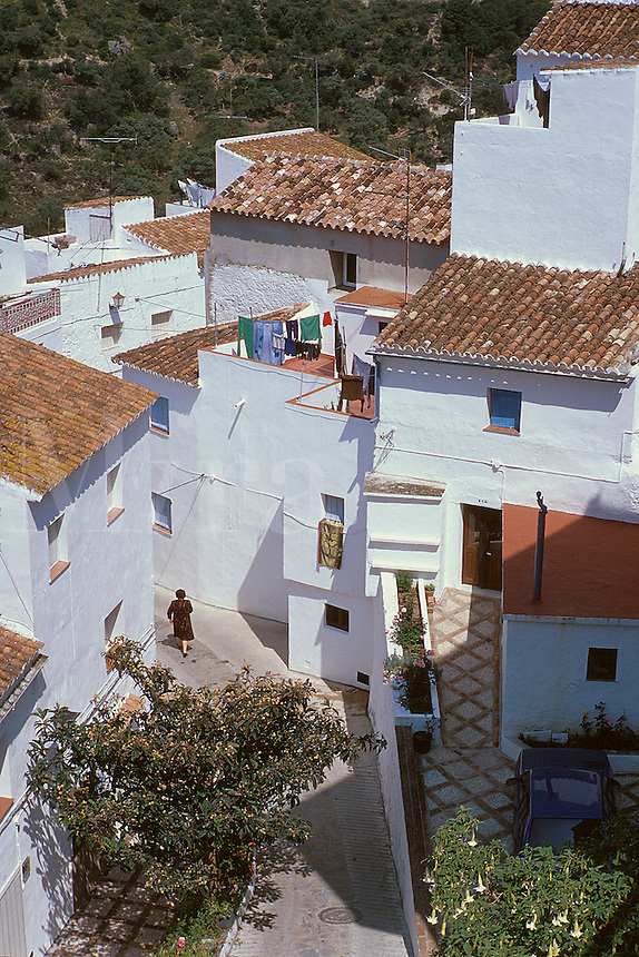 Village scene - white walls, laundry drying, tile roofs, woman walking on narrow street. Casares Andalucia Spain.