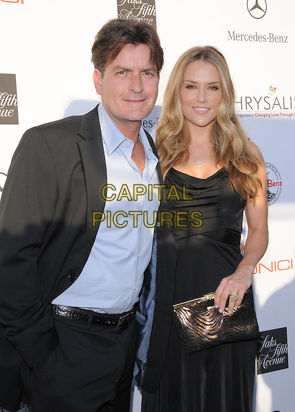 CHARLIE SHEEN & BROOKE MUELLER SHEEN.Attending The 7th Annual Chrysalis Butterfly Ball held at a private estate in Brentwood, California, USA,.May 31st 2008                                                                     .half length black dress suit blue shirt couple clutch bag long .CAP/DVS.©Debbie VanStory/Capital Pictures