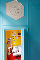 Glimpse of a child's bedroom, painted a bright yellow, in contrast to the turquoise walls of the adjacent sitting room