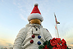 Garden City, New York, USA. December 1, 2013. The NASA astronaut statue, wearing a Santa hat and holding a Christmas wreath for the holidays, is at the entrance to tthe Cradle of Aviation Museum grounds, during the Winter holiday Festival of Trees held at the museum. Event proceeds benefited United Cerebral Palsy Association of Nassau County, Long Island.