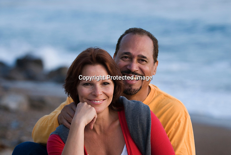 Happy couple at beach, facing camera