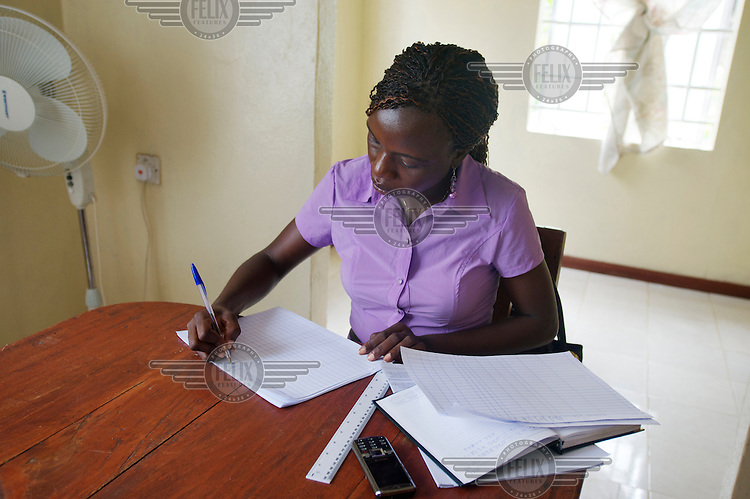 Baindu Koroma, a paralegal who works for Timap for Justice, preparing her work sheets for the day at the office.  <br /> Her work includes making regular visits to police stations, the prison, and the courts to monitor whether people are being afforded their lawful rights, for example, the right to bail, legal representation, detention without charge, etc, and if not to advocate on their behalf.