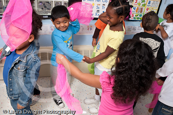 Education preschool 3-4 year olds circle time music activity dancing and waving pink scarves horizontal