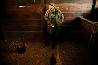 "Wellsville, Kansas, May 28, 2011 - Fourth generation family farmer Robin Dunn talks with her laying hens after pulling an egg from the nest at her farm, Dunn's Landing. .When asked if she ever gets lonely farming alone, she says, ""How could I be lonely with all of these animals to talk to.""..She bought her great grandparents homestead from her father in 1993, and today grows soybeans, corn, sorghum and hay, and maintains a small herd of Black Angus cattle and eight horses which she uses to for wagon and stage coach rides.  According to the most recent Department of Agriculture data, there are more than 306,000 farms run primarily by women in 2007, representing about 14 percent out of the 3.3 million American farms.  That's up from 237,819 or 11 percent in 2002, and a big increase from the 1980s when about five percent of U.S. farms were operated by women.Dunn has branched out from her farming business, using her century-old dairy barn to host 25 to 30 weddings and other events a year. She also attracts tourists for farm tours and carriage rides, and holds sessions with school children to teach them about faming."