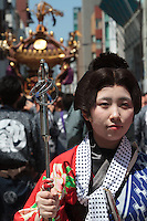 A Japanese woman in traditional dress walks ahead of people carrying a mikoshi, or portable shrine, in the bi-annual Kanda matsuri (festival). Chiyoda Ward, Tokyo, Japan Sunday May 10th 2015. Over 200 mikoshi are carried through the streets of central Tokyo every 2 years in this spring festival