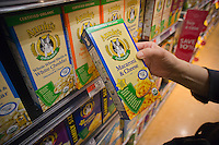 A shopper chooses Annie's Mac 'n Cheese products in a supermarket in New York on Wednesday, March 28, 2012. The organic food company, located in Berkeley CA, went public today offering five million shares. The company specializes in organic foods with its most popular product being mac 'n cheese in the shape of bunnies. The company will trade under the symbol BNNY.  (© Richard B. Levine)