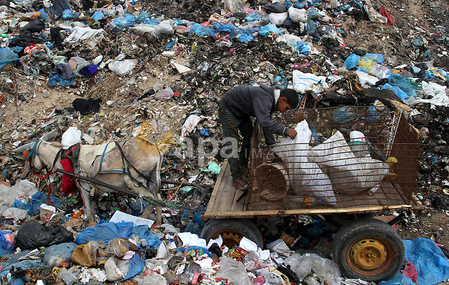 A Palestinian boy searches in the garbage near the border with Israel, east of Rafah town, in the southern Gaza Strip, April 16, 2015. Workers collect the household recyclables, metals and plastic from landfill and garbage to sell to the Israeli and local factories. Photo by Abed Rahim Khatib
