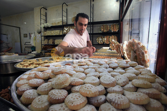 A Palestinian vendor sells cakes at a street market ahead of the Muslim festival Eid al-Adha in the West Bank city of Ramallah, on Oct. 14, 2013.  Eid al-Adha (the Festival of Sacrifice) is celebrated throughout the Muslim world as a commemoration of Abraham's willingness to sacrifice his son for God, and cows, camels, goats and sheep are traditionally slaughtered on the holiest day. Photo by Issam Rimawi