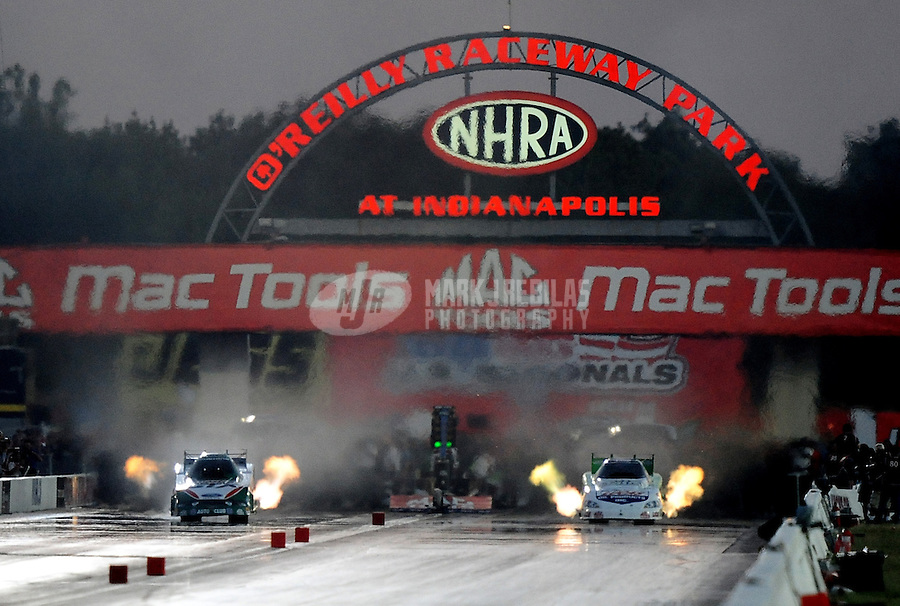 Sept. 4, 2010; Clermont, IN, USA; NHRA funny car driver Ashley Force Hood (left) races alongside Paul Lee during qualifying for the U.S. Nationals at O'Reilly Raceway Park at Indianapolis. Mandatory Credit: Mark J. Rebilas-