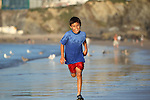 Young boy plays and runs in the surf along an English beach near sunset