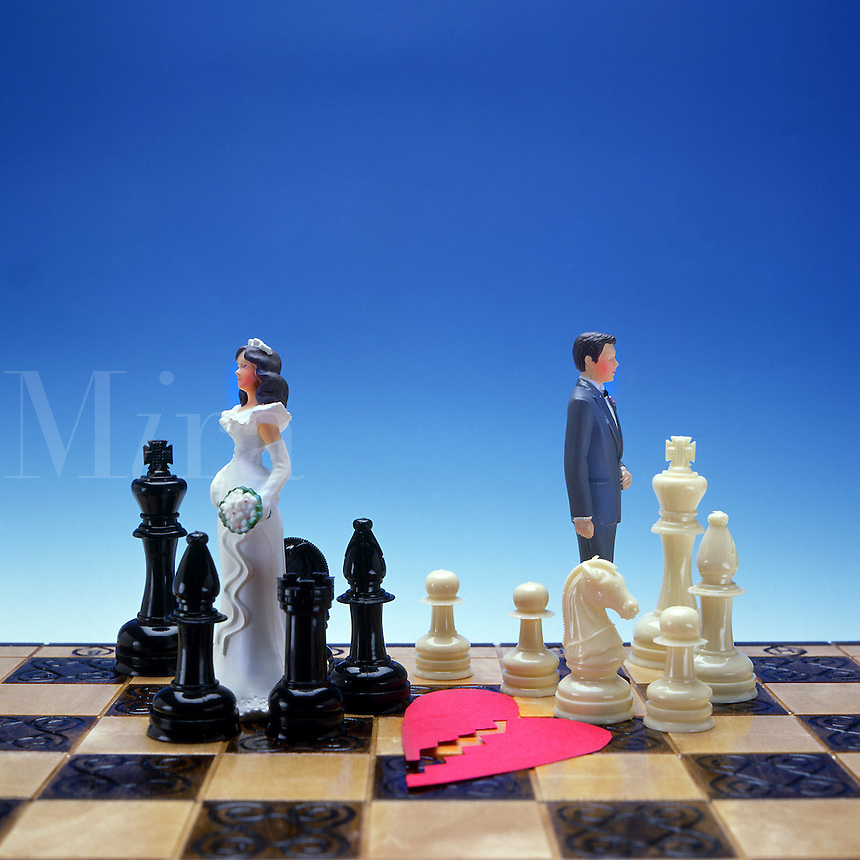 Symbolic portrayal of divorce with bride and grrom  and broken heart to separate pieces in split up of relationship.