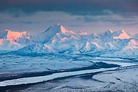Aerial of alpenglow light on the snow covered peak of Mount Hayes, 13,832 feet (4,216 m), the highest mountain in the eastern Alaska Range. View looking southwest.