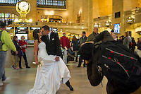 A couple dressed in wedding finery have their picture takes as travelers crowd Grand Central Terminal in New York on Wednesday, November 27, 2013, the beginning of the great exodus over the Thanksgiving weekend.  According to AAA, 43 million Americans will travel 50 miles or more, with Wednesday being the busiest travel day of the year.  (© Frances M. Roberts)