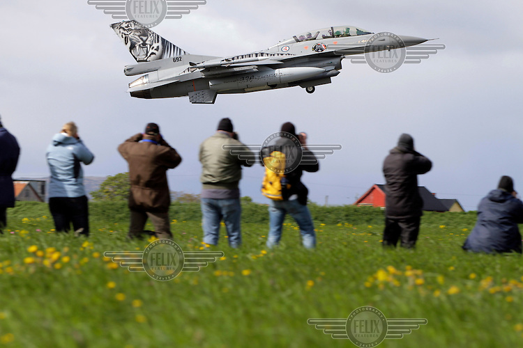 A Norwegian F-16 takes off as plane spotters watch and photograph. Nato Tiger Meet is an annual gathering of squadrons using the tiger as their mascot. While originally mostly a social event it is now a full military exercise. Tiger Meet 2012 was held at the Norwegian air base Ørlandet.