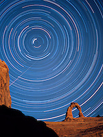 Polaris describes the interior arc of Delicate Arch while uncountable stars of the night sky repeat the pattern in this eight hour time exposure. A meteor is also visible in the upper right of the image. Arches National Park, Uta