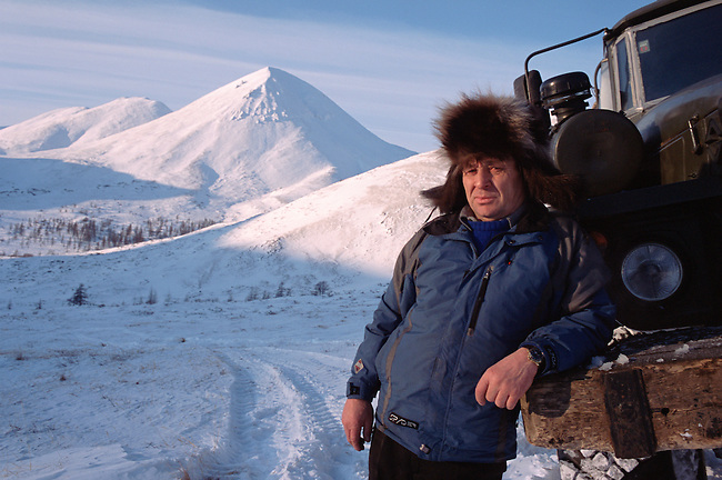 Truck driver, Vassily Nesmelov, takes a break on a winter road in the Kolyma Mountain Range. Magadan Region, E. Siberia, Russia