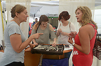 NWA Democrat-Gazette/BEN GOFF @NWABENGOFF<br /> Carianne Schulte (from left), of Austin, Texas makes a few last-minute sales of her sterling silver jewelry to Rachel Davis and mother Julie Heimeshoff of Bella Vista and Tracy Smallwood of Claremore, Okla. on Sunday June 12, 2016 after the Bentonville Art Market in downtown Bentonville was closed early due to rain and lightning. The event, which began on Saturday during the Bentonville Farmers Market, is part of the Downtown Bentonville, Inc. Art and Culinary Festival.