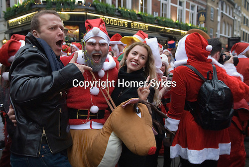 Tourists get photographed with a Father Christmas and Rudolph  the Red Nosed Reindeer. SantaCon meet up outside Liverpool Street Station central city of London UK 2015.