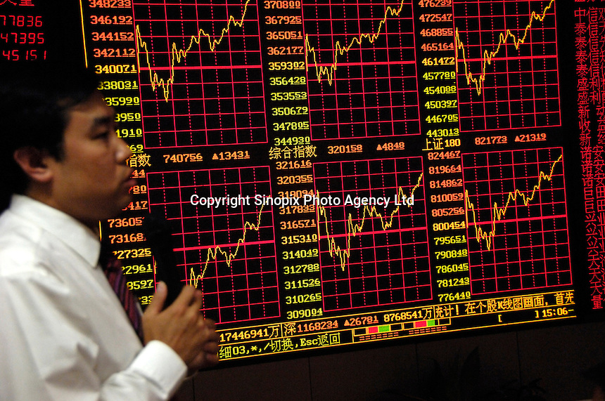 A stock analyst analyzes market to investors at the end of the exchange day in a stock exchange of Beijing. Chinese share prices broke through the psychologically important 4000-mark for the first time ever last week and dealers said the sustained Chinese advance is being driven by massive inflows of fresh funds as smaller investors take their money out of low-return bank deposits and punt on stocks..16 May 2007