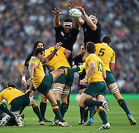 Will Genia of Australia box-kicks the ball as Jerome Kaino and Brodie Retallick of New Zealand look to charge him down. Rugby World Cup Final between New Zealand and Australia on October 31, 2015 at Twickenham Stadium in London, England. Photo by: Patrick Khachfe / Onside Images
