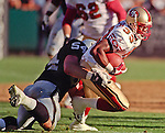 Oakland Raiders vs. San Francisco 49ers at Oakland Alameda County Coliseum Monday, August 30, 1999.  49ers beat Raiders  16-8 in a preseason game.  Oakland Raiders linebacker Greg Biekert (54) tackles San Francisco 49ers running back Lawrence Phillips (33).