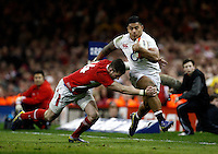 Photo: Richard Lane/Richard Lane Photography. Wales v England. RBS 6 Nations Championship. 16/03/2013. England's Manu Tuilagi is tackled by Wales' Alex Cuthbert.