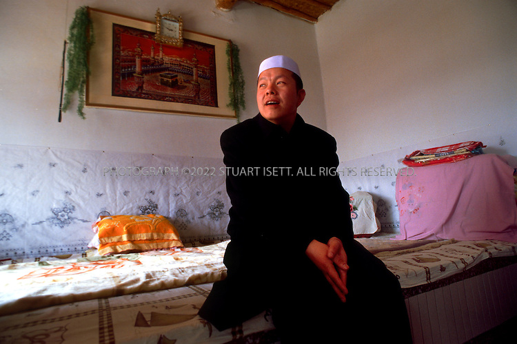 3/14/2004--Ma Village, Ningxia Province, China..Sheik Hong Yang (39) head of the Hufuye muslim sect in China's arid Ningxia Province waits in the home of a sect member to bless a wedding...With nearly a million members, the Hufuye sect is one of many religious groups expanding under greater religious freedoms in China although most still fear government crackdowns and follow Beijing's line...Photograph by Stuart Isett     .©2004 Stuart Isett. All rights reserved