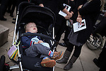 © Joel Goodman - 07973 332324 . 02/09/2013 . Bury , UK . A boy sleeps in a pushchair as mourners clutching copies of the order of service stand around him . The funeral of fireman Stephen Hunt at Bury Parish Church today (Tuesday 3rd September 2013) . Stephen Hunt died whilst tackling a blaze at Paul's Hair World in Manchester City Centre in July 2013 . Photo credit : Joel Goodman
