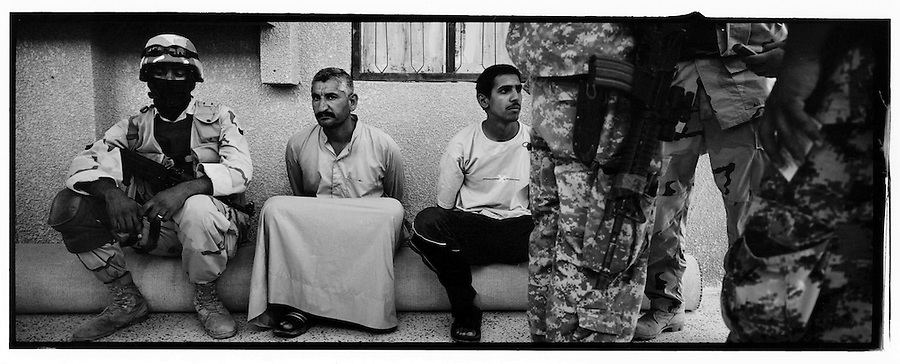 Iraqi soldiers and police guards two being held for questioning following the discover of a cache of weapons by soldiers with 4BN 23rd Infantry Regiment 172nd Stryker Brigade during the search of a mosque in the Baghdad Sunni neighborhood of Ghazaliyah on Wednesday August 16, 2006.  The raid, which yielded weapons and IED making materials, was part of an operation by bolstered US and Iraqi forces carried out in the hopes of putting a stop to the extraordinary numbers of sectarian killings in Baghdad.