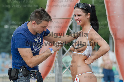 Body painting artist Gergo Pal (L) decorates a topless participant Petra Viktoria Ihasz (R) during the Miss Bikini Hungary beauty contest held in Budapest, Hungary on August 06, 2011. ATTILA VOLGYI