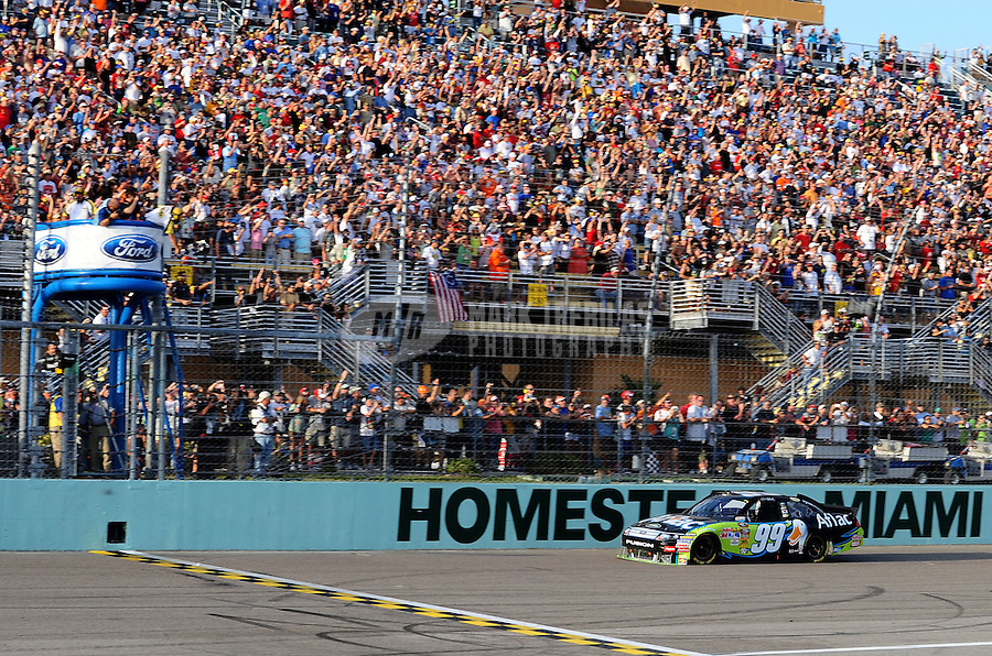 Nov. 21, 2010; Homestead, FL, USA; NASCAR Sprint Cup Series driver Carl Edwards takes the checkered flag to win the Ford 400 at Homestead Miami Speedway. Mandatory Credit: Mark J. Rebilas-