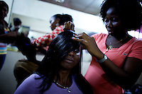 """A customer has her hair styled at the """"Downtown beauty salon"""" where several Nollywood stars frequently have their hair styled by head hair dresser Agnes Adamson and her staff in Lagos, Nigeria on Friday March 27 2009..Currently the most requested hair styles at the salon are """"Take a bow"""" and Crazy Alia""""...Currently, Nigerian films outsell Hollywood films in Nigeria and many other African countries..Nollywood is a nascent film industry in Nigeria, growing up within the last two decades to become the third largest film industry on the planet, behind the United States and Indian film industries. Nigeria has a US$250 million movie industry, churning out some 200 videos for the home video market every month."""
