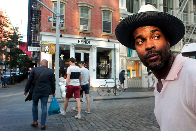 MANHATTAN, NY - AUGUST 25: Photographer Karl-Edwin Guerre looks for street fashion to photograph in passersby in the SoHo neighborhood of Manhattan, NY, on August 25, 2015. (Photo by Yana Paskova/For The Washington Post)