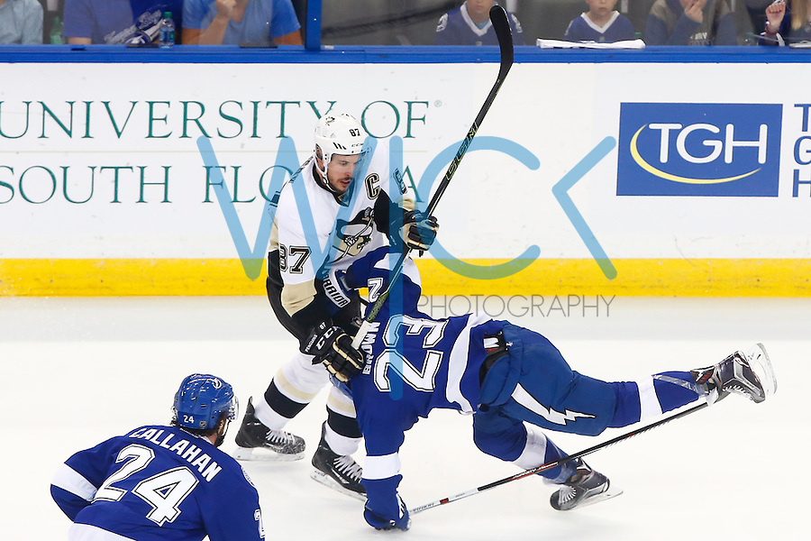 Sidney Crosby #87 of the Pittsburgh Penguins hits J.T. Brown #23 of the Tampa Bay Lightning in the first period during game four of the Eastern Conference Finals of the Stanley Cup Playoffs at Amalie Arena in Tampa, Florida on May 20, 2016. (Photo by Jared Wickerham / DKPS)