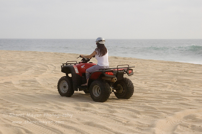 Woman riding a Quad on the playa near Migrino, Baja California, Mexico