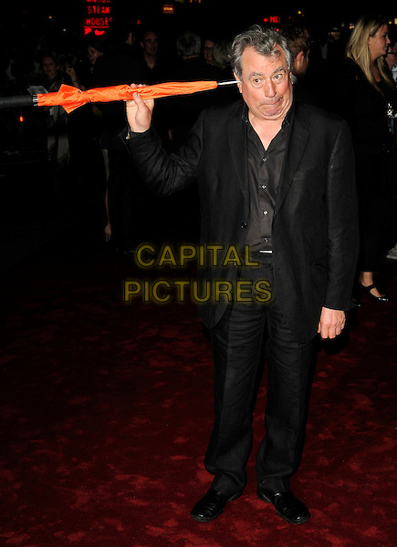 "TERRY JONES .Attending the UK film premiere of ""The Imaginarium Of Doctor Parnassus"" at the Empire Leicester Square cinema, London, England, UK, October 6th 2009..full length black suit brown shirt orange umbrella holding  sticking in ear funny .CAP/CAN.©Can Nguyen/Capital Pictures"