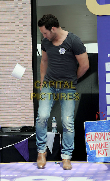 ANTONY COSTA of BLUE .Blue at the Cadburys Spots and Stripes Toilet Roll Challenge at Westfield Shopping Centre, London, England, UK,16th April 2011..full length black grey gray  t-shirt jeans kicking loo roll funny brown shoes .CAP/WIZ.© Wizard/Capital Pictures.