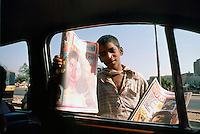 Indian boy selling magazines in the street in Delhi, India