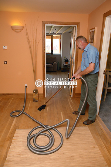 Man using central vacuum cleaning system; designed to expel dust; dirt; mites & pollen from the house; in Eco House at The Wintles; Bishop's Castle,