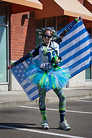 Happy woman Seahawks fan wearing tutu holding 12th man flag, Seahawks 12K Run 2016, The Landing, Renton, Washington, USA.