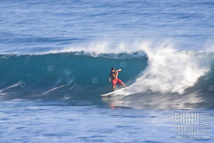 Surfer in red shorts riding a wave backside at a surf spot in Waipio Valley