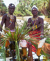 A pair of Masai stand beside a laid table with the river as a backdrop
