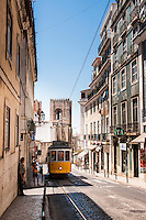 A typical streetcar (trolley) climbing a narrow street from Lisbon's cathedral, Lisbon, Portugal. Although Lisbon has a modern fleet of trams, climbing the steep hills and narrow streets of Lisbon is mostly done in small streetcars, that remain faithful to their style since their first uses in the city, including even the wooden benches and driving system inside. Shown is the world famous line 28, selected by National Geographic as one of the top 10 trolley rides in the world.
