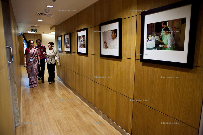 Colleagues walk down the passageway lined with photos of projects at the new Bill & Melinda Gates Foundation office in New Delhi, India on 17th December 2010. Photo by Suzanne Lee for Gates Foundation