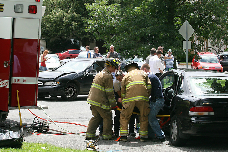 LITCHFIELD, CT - 24 July, 2009 - 072309MO01 - Rescue crews extricated Rabbi Joseph Eisenbach from a Toyota Avalon Friday after a two-car crash next to the Litchfield Green. Police said Eisenbach suffered injuries not believed to be life-threatening. The four occupants of the Nissan Altima that struck Eisenbach's car are seen standing in the background from left, and declined medical attention. Police said Eisenbach pulled out on to Rt. 202 from Meadow Street in front of the oncoming Nissan Altima driven by a Terryville man. Jim Moore Republican-American.