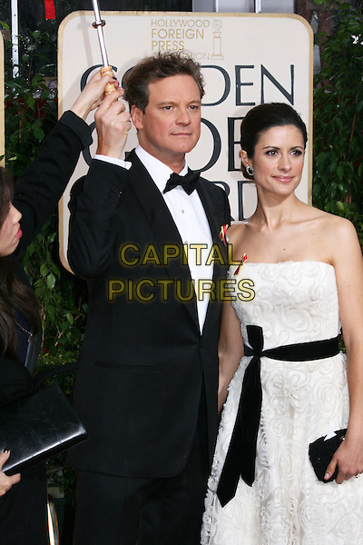 COLIN FIRTH & LIVIA GIUGGIOLI.Arrivals at the 67th Golden Globe Awards, he Beverly Hilton Hotel, Beverly Hills, California, USA, .January 17th, 2010..globes half length black tuxedo jacket bow tie married husband wife ribbon sash waist white strapless dress umbrella raining clutch bag 3/4 .CAP/AW/MAZ .©Maz/Weber/Capital Pictures.