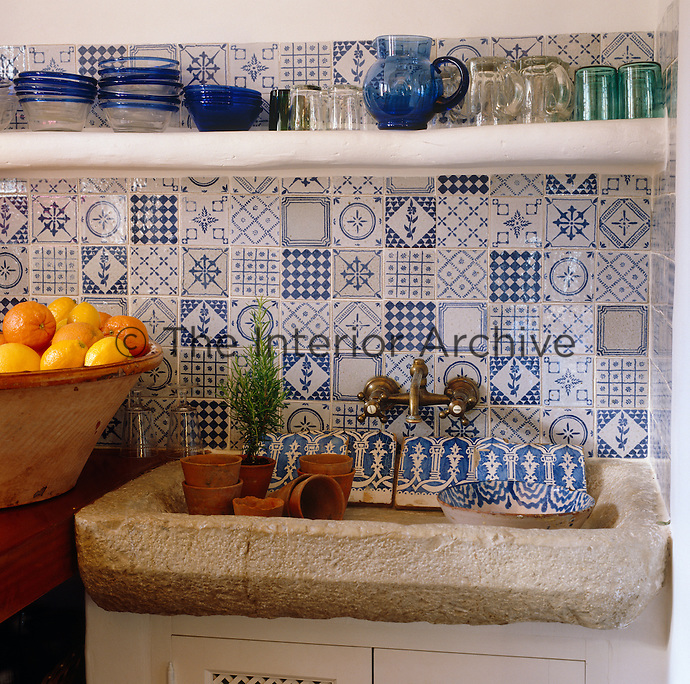 The wall behind the sink of rough hewn stone is covered in blue and white glazed tiles